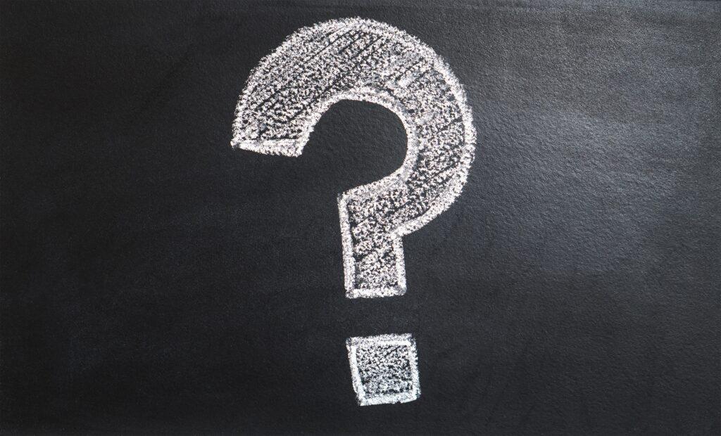 Question Mark in White Chalk on Blackboard.